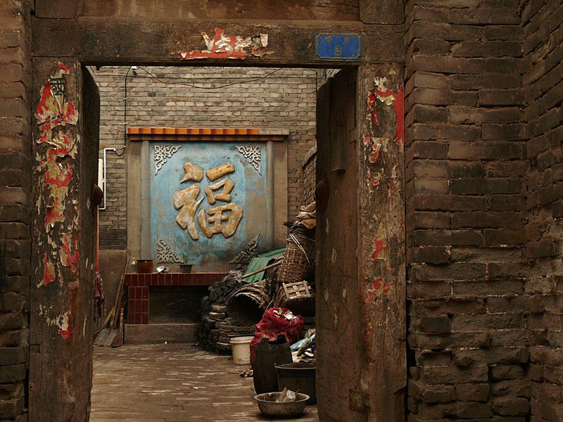 Behind the doors of Pingyao, China - Pingyao's four main streets are lined with tourist shops, cafes, and hotels. But step off of them into the warren of its narrow ancient streets, and walk back into time itself.