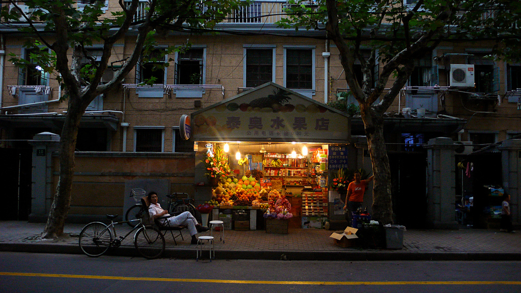 Fruit Stand, Shanghai, China - On a quiet, tree-lined street in Shanghai's 19th Century French Concession, fruit vendors wait for customers on a long summer evening.
