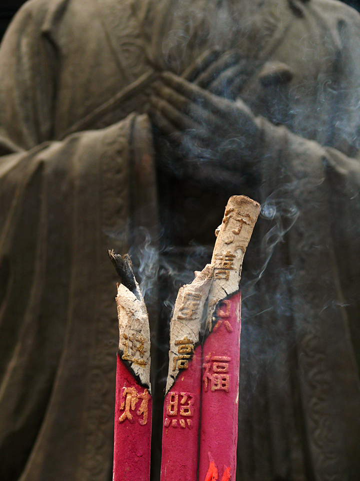 Confucian Temple, Nanjing, China - Huge sticks of incense constantly burn before the statue of Confucius in Nanjing's 1,500 year old Confucian Temple. The characters imprinted on the outside of the sticks appear as well on the burning ash itself.