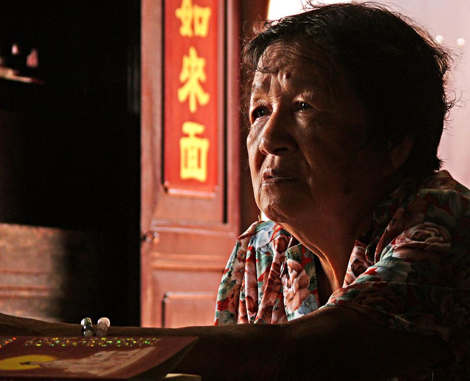 Temple portrait, Malacca, Malaysia - This woman was engaged in a long and active discussion just inside the entrance to Malacca's historic Cheng Hoon Teng Temple. She knew that four photographers were shooting her simultaneously yet showed no signs of either self-consciousness or annoyance.