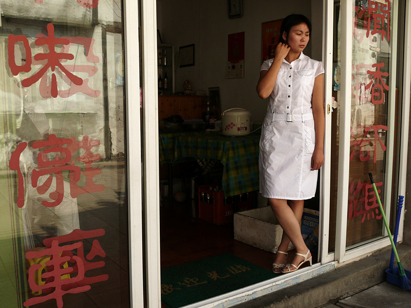 Waitress, Feng Jing, China - This young waitress works in a small restaurant just outside the gate to this old city. She waits to greet customers -- this day, they are far and few between.