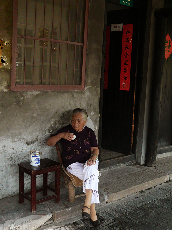 Tea time, Feng Jing, China - This gracious lady showed great patience -- we trained our cameras on her for over ten minutes, without any complaint or distress. Her house is hundreds of years old.