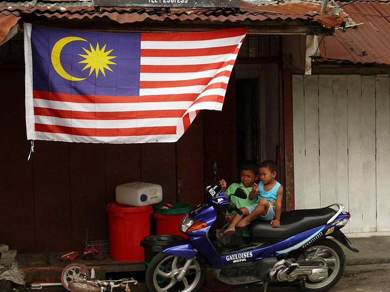 Slow riders, Kuala Lumpur, Malaysia - These young boys were making all the right noises as they roared along an imaginary road in KL's old Malay quarter, the Kampung Baru. Even the Malaysian flag seems to flutter in response to their dream.