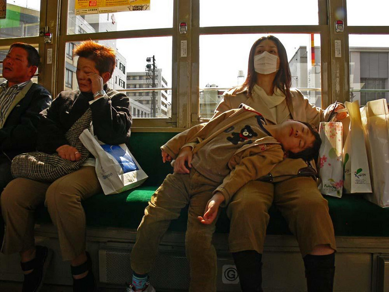 Asleep on the streetcar, Hiroshima - This young boy is sound asleep on his mother's lap. Like many Japanese women, she wears a mask as health measure.