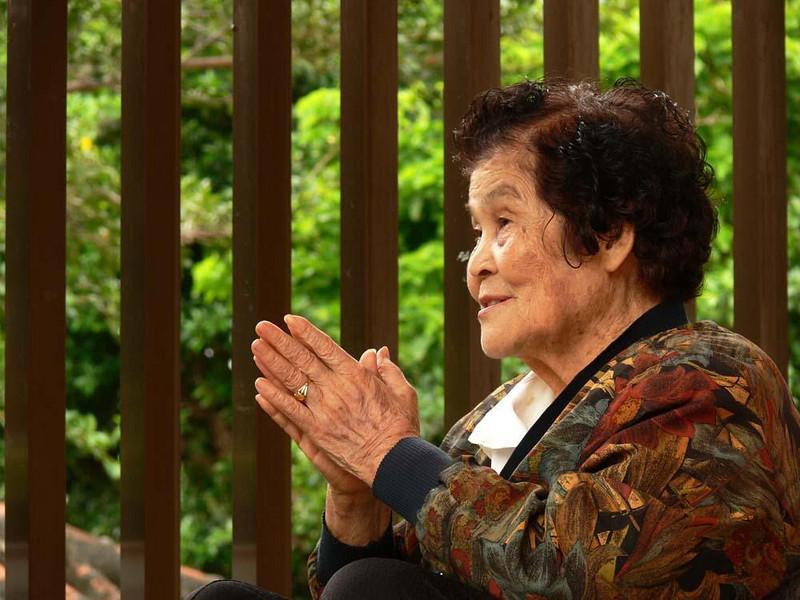 At prayer, Naha, Okinawa, Japan - A woman prays in a Buddhist shrine in Naha