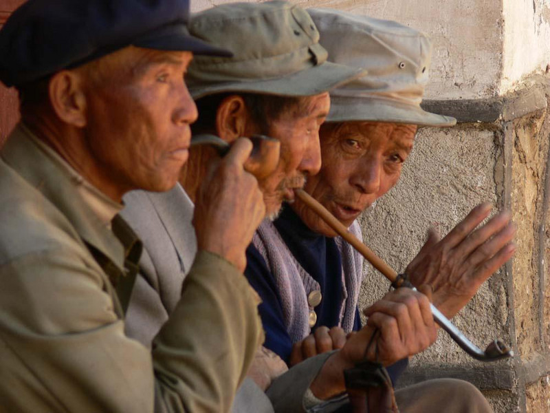 Pipefest, Baisha - This trio of Naxi farmers share a leisurely chat and several pipes filled with local tobacco.