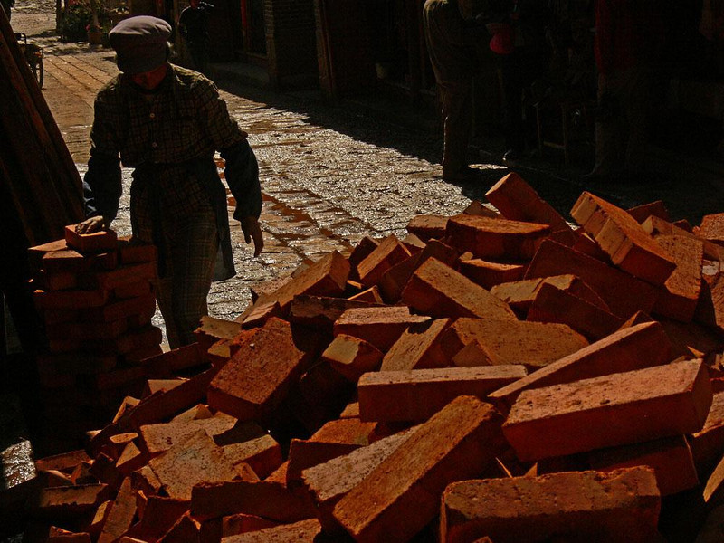 New bricks, Shuhe - A huge pile of new bricks fills a Shuhe street from curb to curb. Women will carry them on their heads to a nearby construction site.
