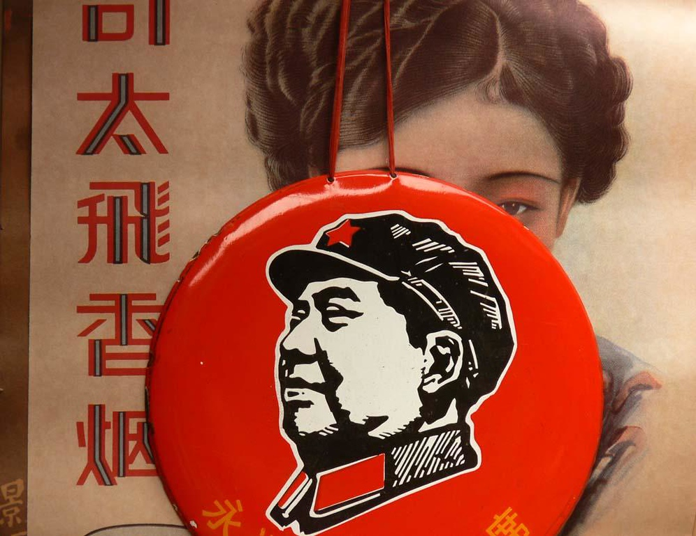 Clashing portraits in Old Shanghai - A huge Mao button can't quite hide the allure of a vintage advertisement on the wall of an Old Shanghai antique stall.
