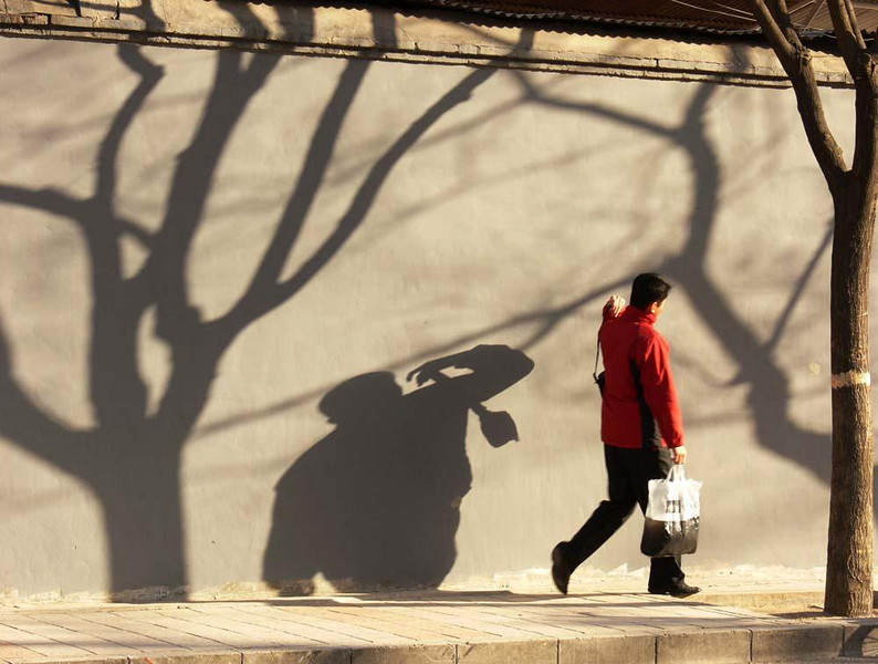 Shadowy visitor - The morning sun casts long shadows in Old Beijing. This camera toting tourist is getting a head start on a long day.