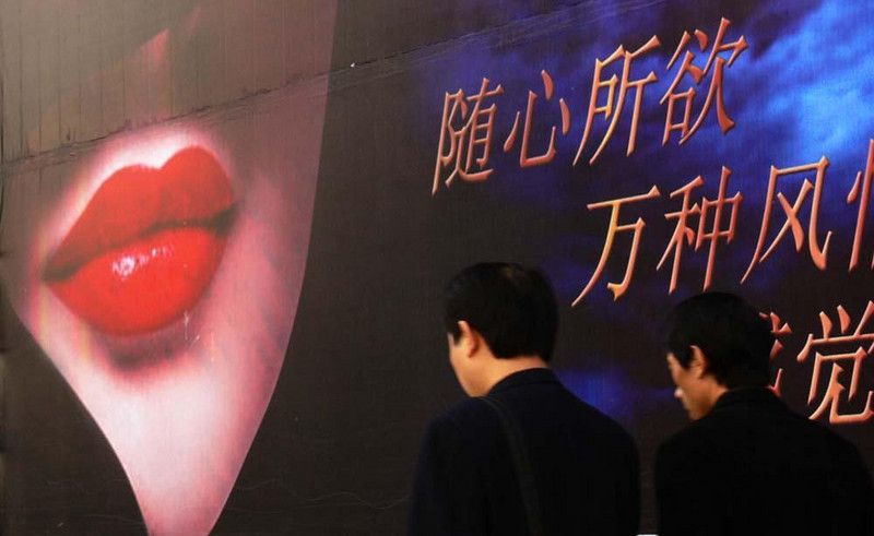 An unspoken message on a Beijing wall - Passers by seem oblivious to the seductive blandishments of this billboard on Beijing's Wangfujing Avenue. The advertisement is for a night club in a local hotel.