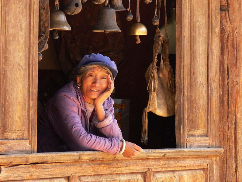 Bell shop, Shuhe - The people of Lijiang and its surrounding villages are still curious about westerners. Other parts of China are accustomed to visitors from the US and Europe, but not here. Many people, such as this woman in a local bell shop, looked at me with curiosity.