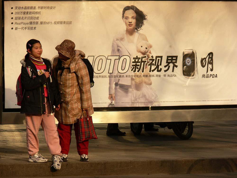 Beijing bus stop - Pedestrians gather on both sides of this billboard near a bus stop in the heart of busy Beijing.