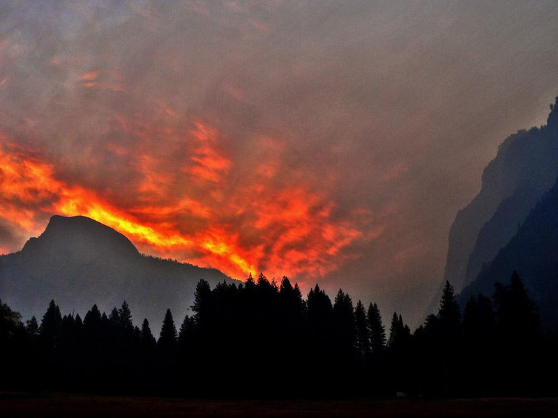 Fiery Dawn at Yosemite - I walked to a meadow in the dark, put my camera on a tripod, and waited for the sun to light up the sky behind Half Dome. I never expected to see, let alone photograph, a sight such as this. I used a long telephoto lens to make this image.