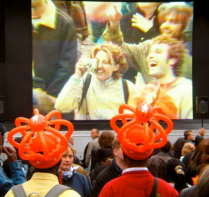 Queens Day fun in Dam Square - Queens Day celebrants wearing inflated plastic crowns watch other celebrants take pictures of themselves as they appear on a giant television screen in the middle of Amsterdam's Dam Square.