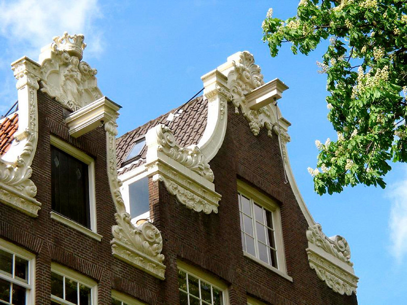 "Gables and hoists, Begijnhof - A close look at two of Begjinhof's 17th Century houses shows how the facades, embellished with ornate ""neck"" gables, disguise the steepness of the roofs behind them and make them look wider, as well as make their owners look wealthier. The only way to get large items into their upper floors was to hoist them up with winches -- still jutting out from the center of each gable."