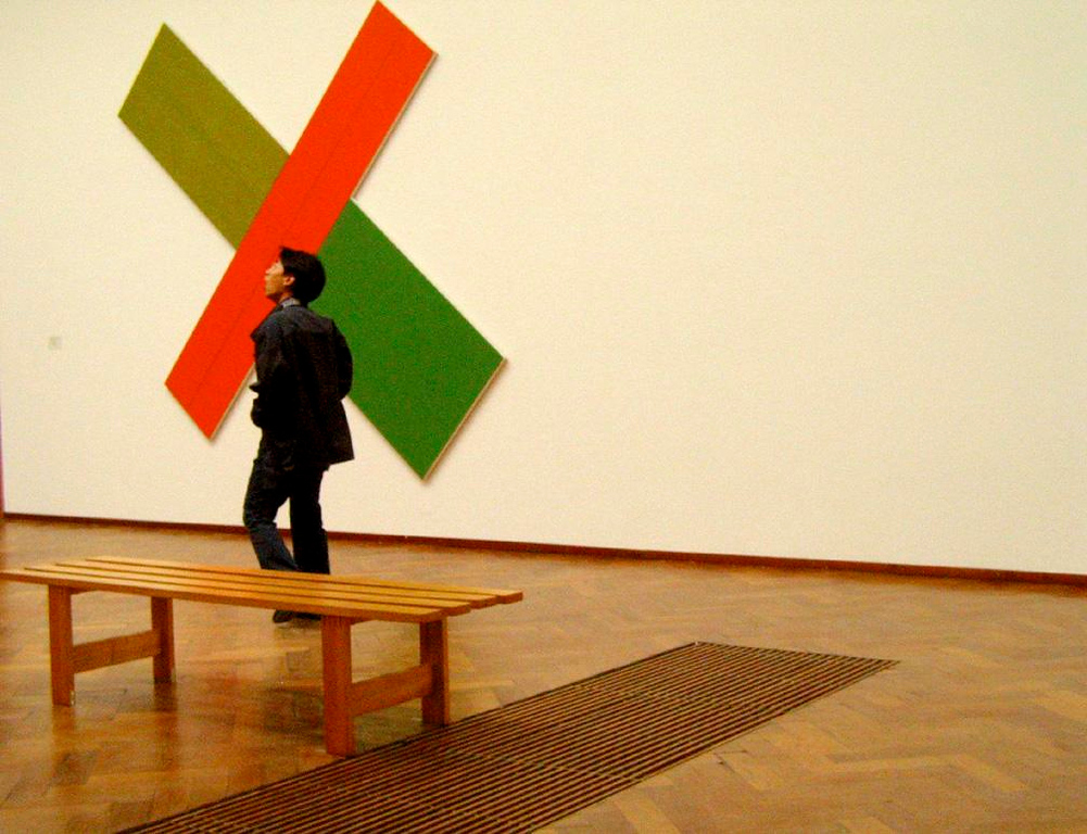 X Marks the Spot - I enjoy making my own art of people enjoying the art of others. As I entered this gallery in Amsterdam's Stedelijk Museum, I noticed the geometric patterns created by the carpet, bench, and the X on the wall. I framed this shot, then waited a few moments for a visitor to step into my composition, completing the picture.