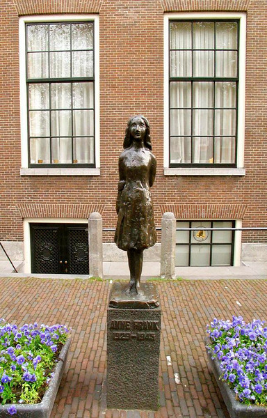 Remembering Anne Frank - A small statue of Anne Frank stands between the flower beds outside the Westerkirk, just around the corner from the house next to Amsteram's Prinsengracht Canal in which she hid until her betrayal to the Nazi's during World War II. The house itself is now a museum to her memory. (Photographs are not allowed to be made within it.) Hiding in the attic of that house, 13-year-old Anne Frank began her now famous diary, a unique account of life under persecution and confinement. It has been since been translated into dozens of languages and made into plays and movies. Anne Frank died in Germany's Begen-Belsen Concentration Camp in March, 1945. The tiny house, which draws a half million visitors a year, has been stripped of its furnishings. Only Anne's collection of film-star pictures remain, pasted to wallpaper, just as she left them.