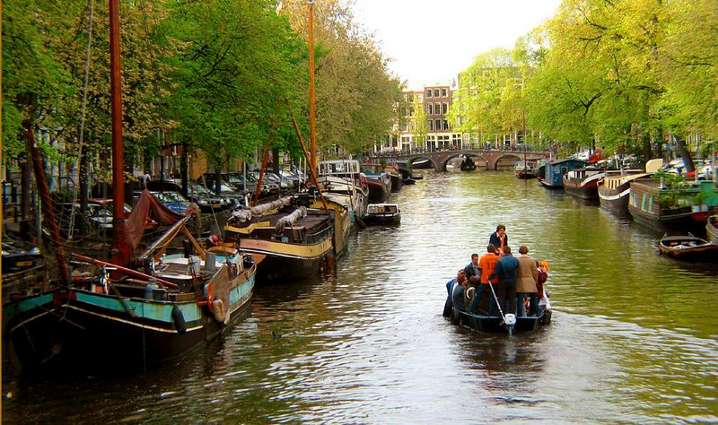 Through a floating neighborhood - Amsterdam's canals are lined with more than 3,000 houseboats, most of which have postal addresses and use city electricity.