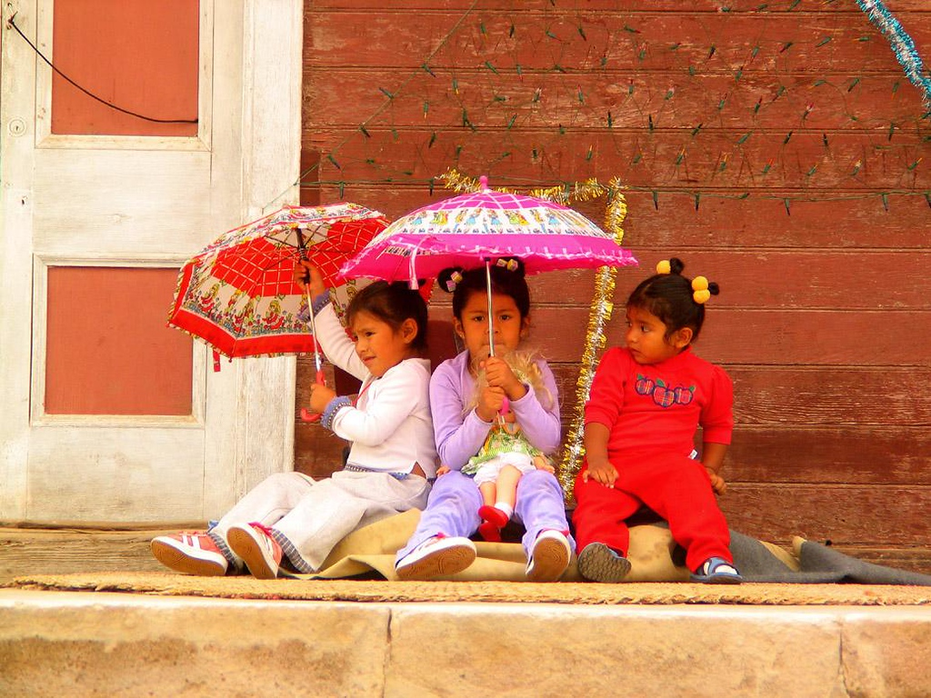 Welcoming Committee, Poconochile, Chile - Three young ladies, dressed in their best clothes, greet an arriving trainload of tourists from Arica with colorful umbrellas at the small Northern Chilean village of Poconchile on the edge of the Atacama Desert.