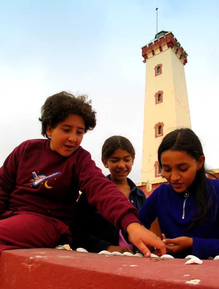 Shell Game, La Serena, Chile - Children play with seashells near La Serena's symbol, the old lighthouse. La Serena is one of the Chile's oldest cities, and has become a prosperous beach resort.