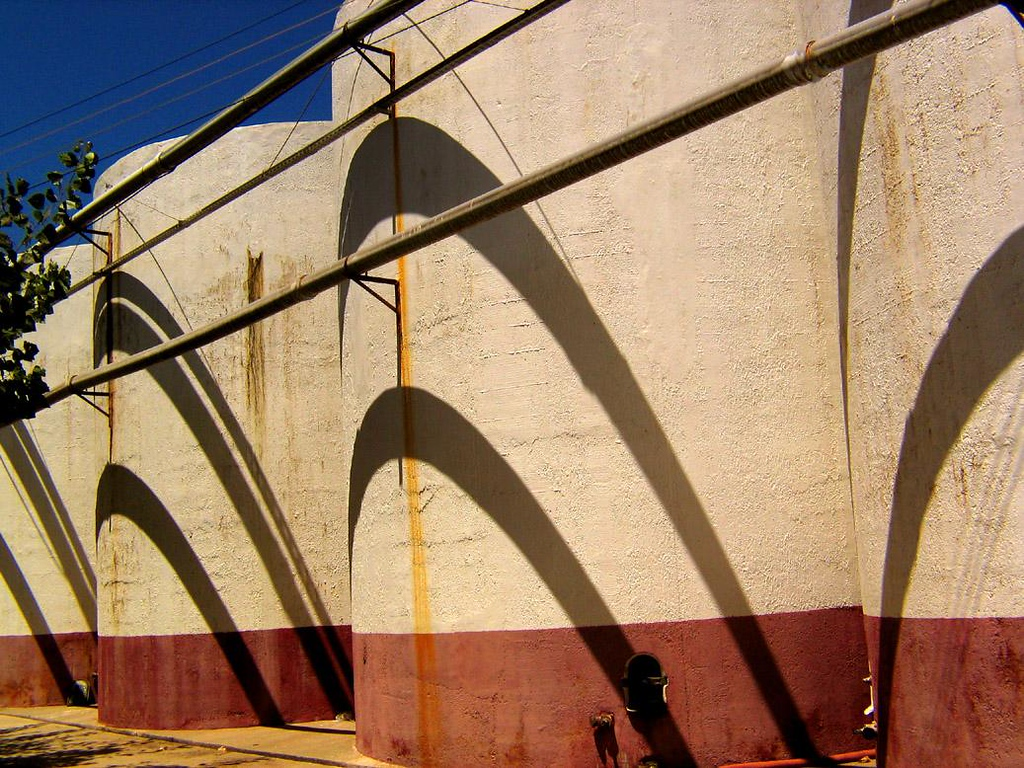 Distillery Tanks, Elqui Valley, Chile - This distillery features rows of new storage tanks, each of them temporarily decorated by the striking shadows cast by the overhead rows of pipes.