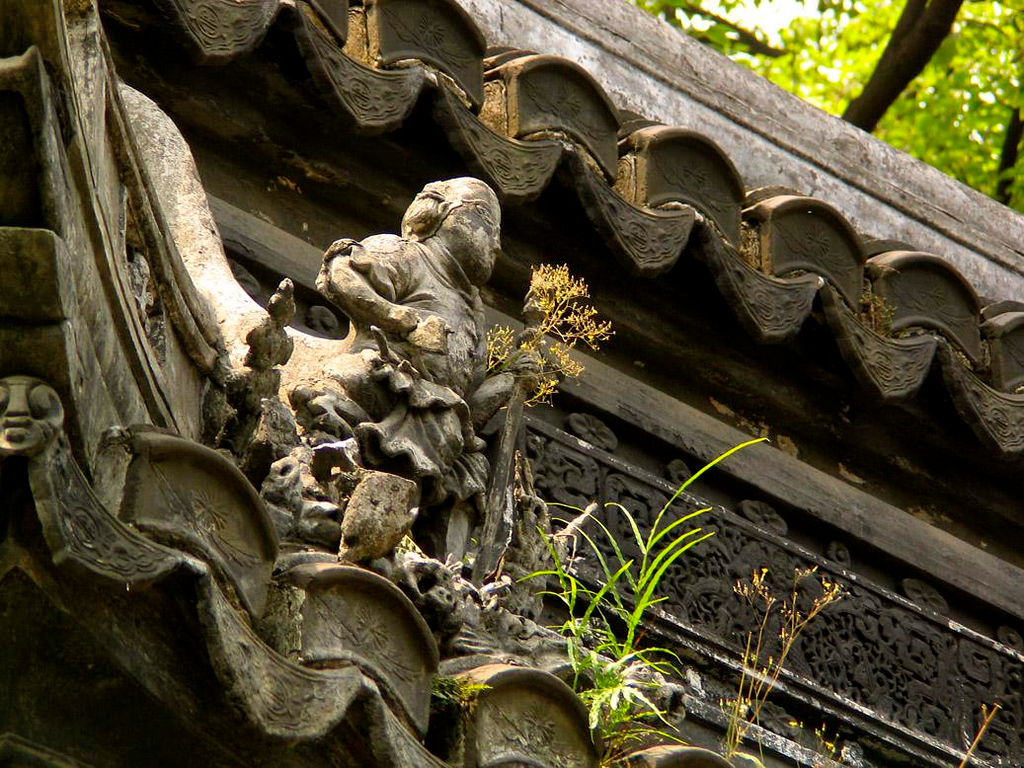 "Roof Figure, Yuyuan Gardens - Buildings dating back as far as the 16th Century still stand in these gardens that lie at the heart of Shanghai's ""Old City"". A closer look finds weeds growing out of the worn sculptures that adorn these ancient structures."