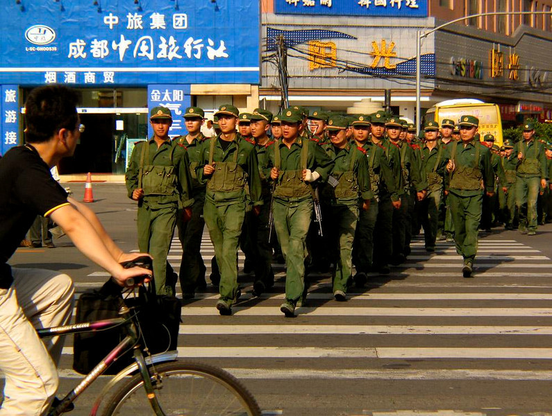Chinese Army in the streets of Chengdu - The Army of the People's Republic of China made an sudden appearance in downtown Chengdu while I was there, and marched directly towards me while I was waiting at an intersection. A civilian cyclist waiting for the traffic light to change was stunned as well. (I have no idea why the fellow in the second row on the right is making that awful face -- perhaps he would rather be someplace else at the moment?)