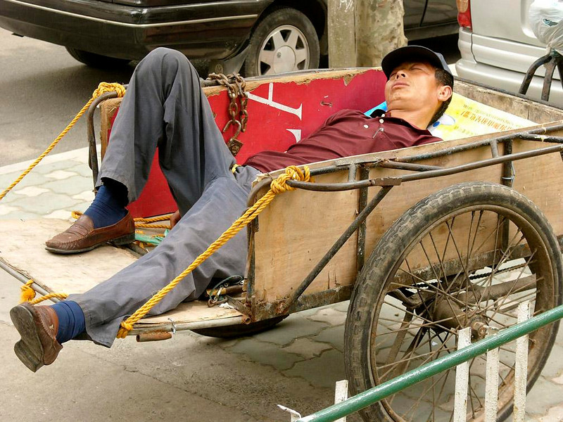 Lunch break, Shanghai - A cart makes a handy bed for this Shanghai worker on lunch break.