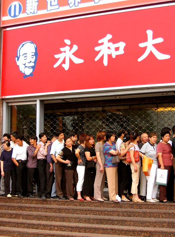 Lining up for KFC - A crowd shows up early at a Shanghai Kentucky Fried Chicken outlet. American fast food has become enormously popular in China.