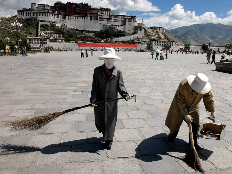 Street sweepers, Potala Plaza - Except for a few passing tourists, the vast plaza facing Lhasa's Potala Palace is the domain of masked street sweepers wielding straw brooms.
