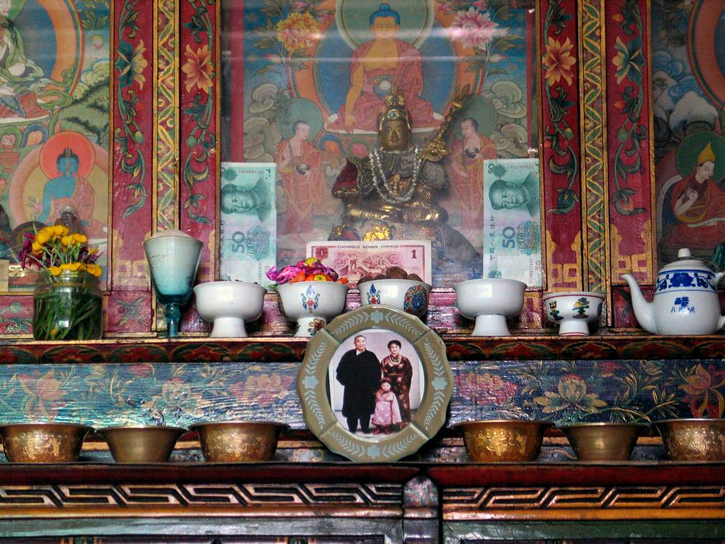 Shrine, Tibetan home - In the bedroom of the home of the woman we visited in Lhasa, I noticed a prayer shrine, filled with not only ceremonial objects, but also monetary offerings and a photograph of the late Panchen Lama and his family. Ironically, the figure on the money, Mao Zedong, once ruthlessly persecuted Tibetan Buddhists and imprisoned this Panchen Lama, Tibet's second ranking cultural and religious leader, for ten years.