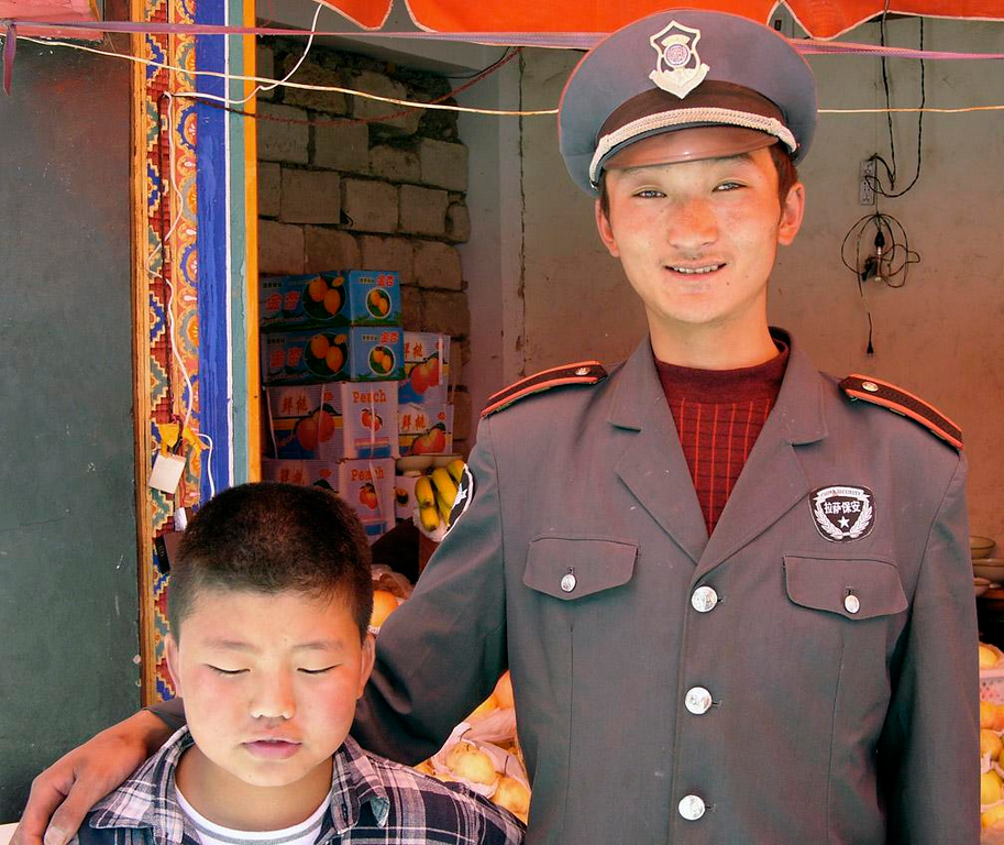 Security Guard and friend, Lhasa - This Lhasa security guard noticed my camera, and through a series of gestures insisted that I take his picture posing with a shy boy. (It could even be his little brother.) In any event, the kid would have none of it. I took this picture four times and he never opened his eyes.