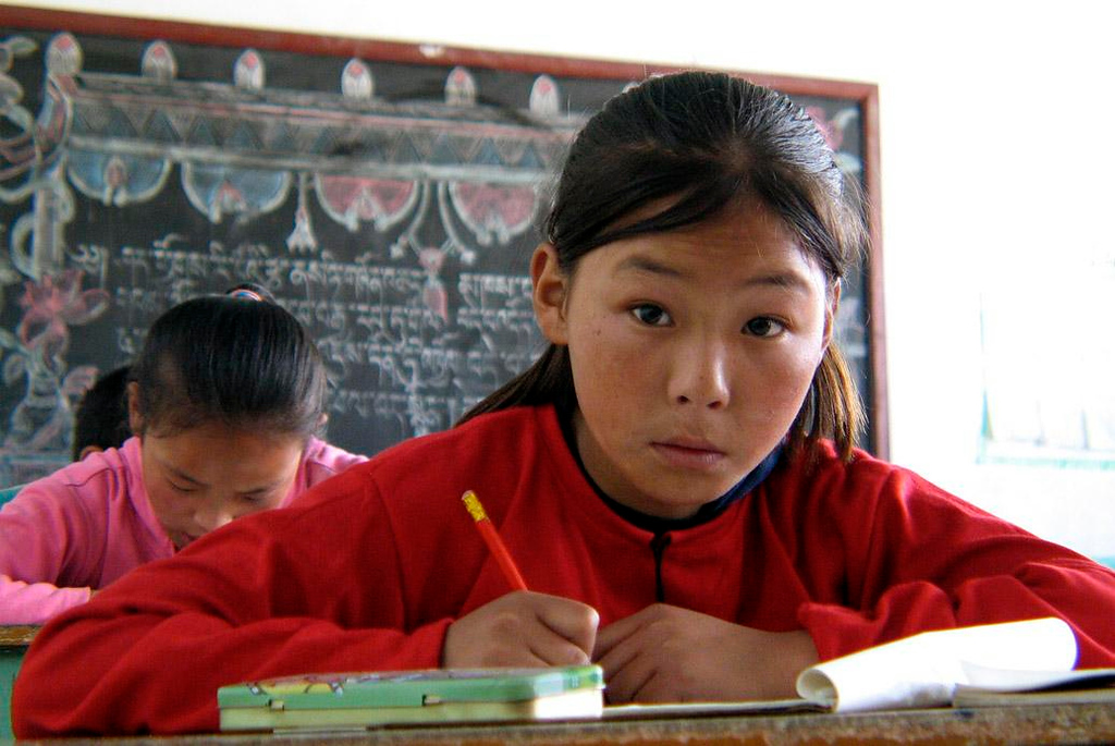 Student, Special Needs School, Lhasa - We visited the only boarding school for children with special needs in all of Tibet, and spent a hour or so in its classrooms. I will never forget the face of this student as she looked up from her work at me.