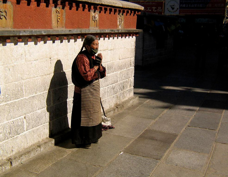 Prayers, Jokhang Temple, Lhasa - Tibet's spiritual leader, the Dalai Lama, fled to India in 1959. In exile, he has persuaded China to allow Tibetans a degree of religious freedom, such as this woman's right to pray at the Jokhang Temple.