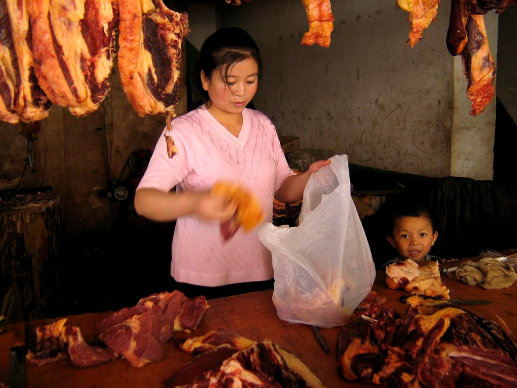 Role model, Lhasa - Watching his mother pack up a bag of meat, this butcher's son is already learning his future trade.