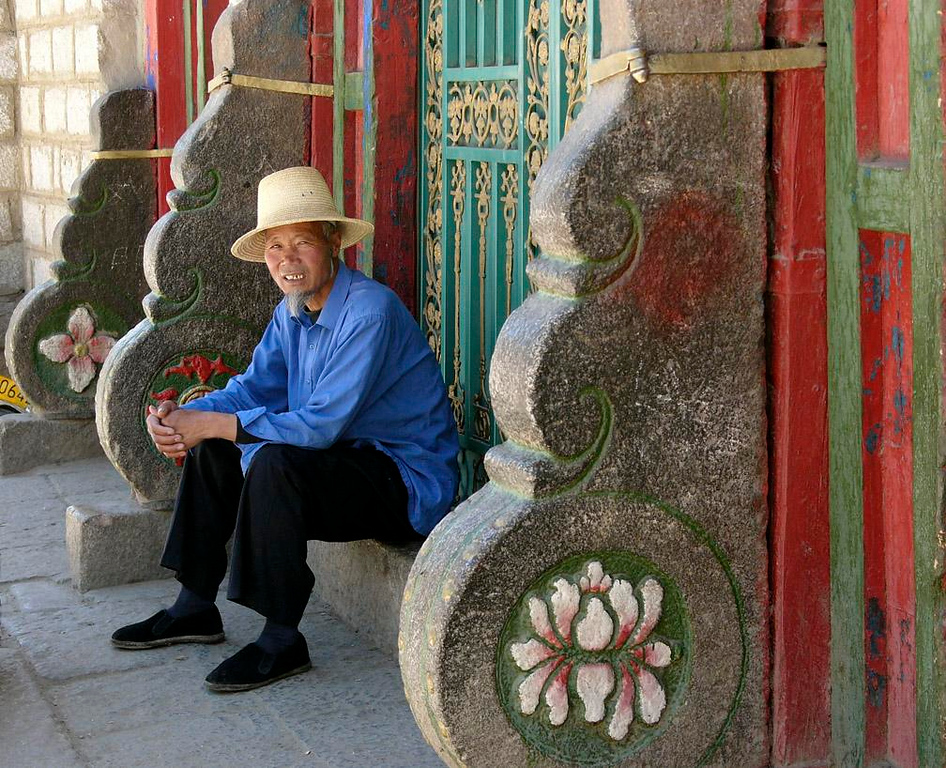 Tibetan gentleman, Lhasa - Tall straw hat, wispy goatee, long shirt, a seat on the steps of a neighborhood temple, and an utterly relaxed attitude add up to a complete portrait of a Tibetan gentleman.