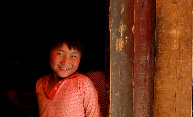 Tibetan child, Lhasa - A young girl, framed in the doorway of her Lhasa home, was delighted to be the subject of a photograph.