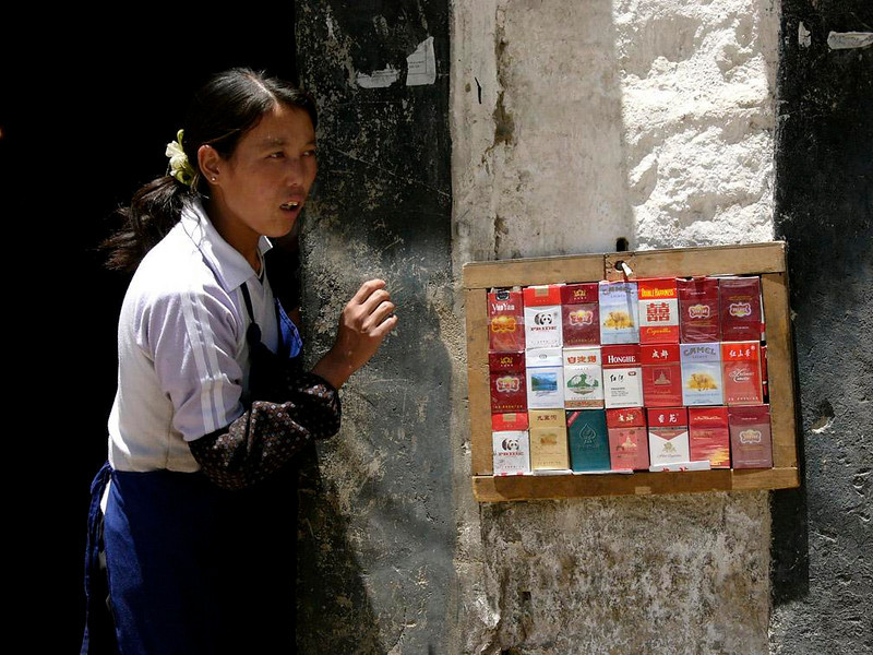 Decision time, Lhasa - This rack of cigarettes, mounted just outside of the door of a Lhasa shop, helps customers who are in a hurry. This store clerk will pluck a pack from the rack as soon as the customer makes his choice.