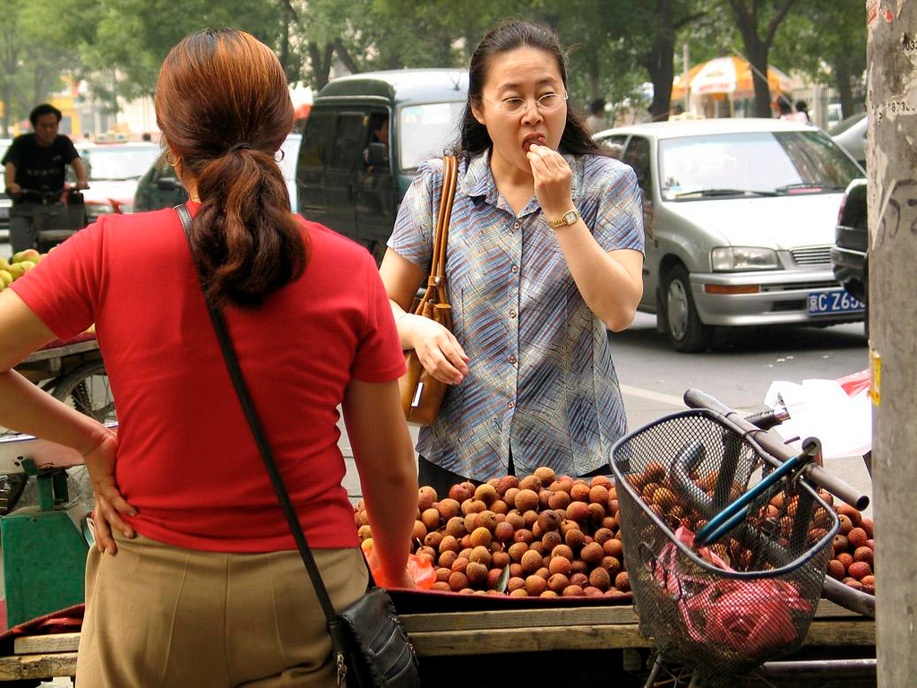 Lichee Tasting - On this Beijing street corner, a woman gets to taste the lichee before she buys.