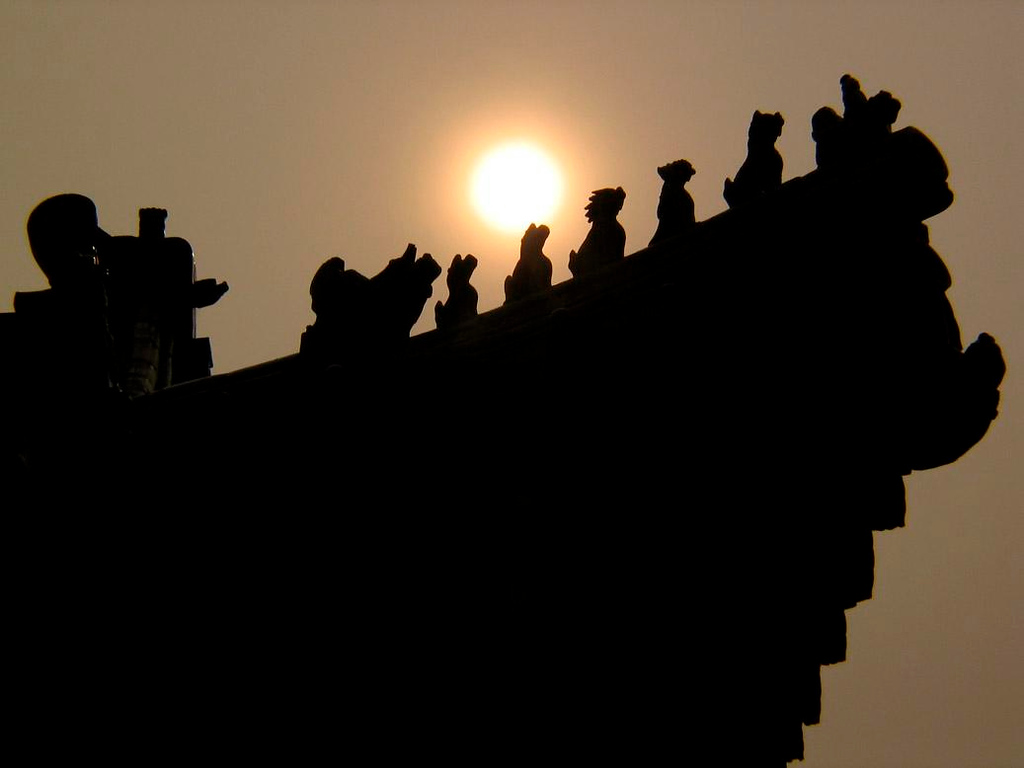 Roof at Temple of Heaven - The sun burns through the late afternoon haze to backlight the ceramic animals that have been guarding the rooftops of the Temple of Heaven complex since 1430.