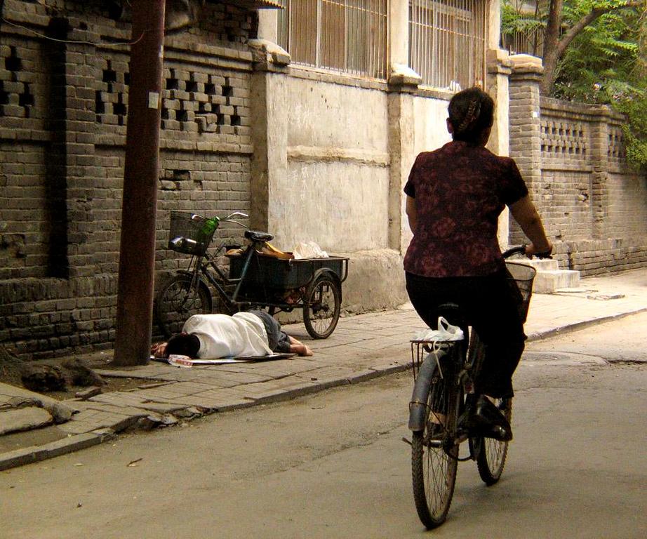 Street sleeper, Beijing - A delivery man takes a nap break on a Beijing street.