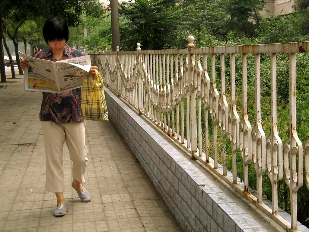 News in Beijing - Utterly absorbed by the day's news, a woman walks and reads at the same time.