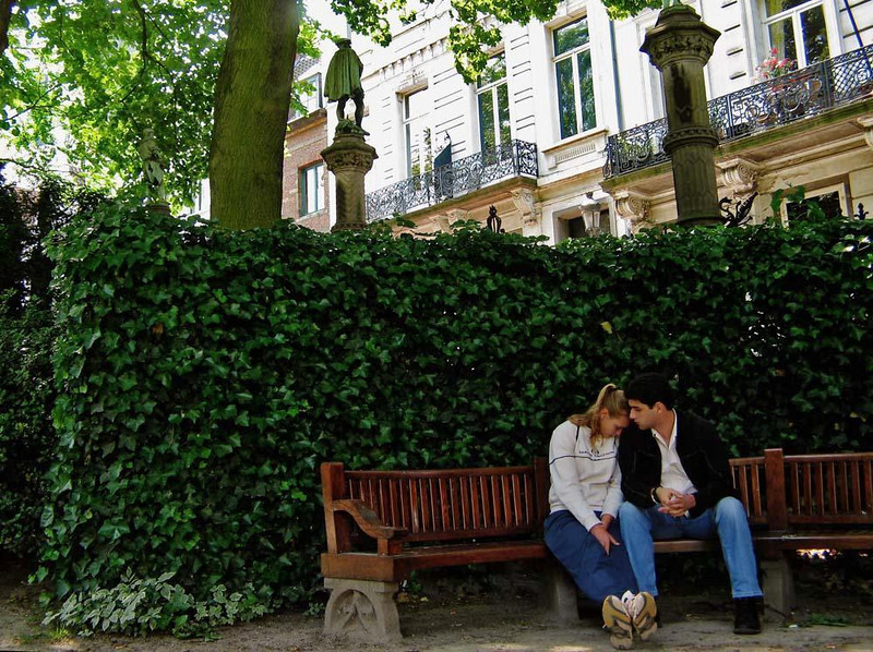 Moment in the Petit Sablon - This small Victorian park in Brussels upper town offers a charming spot to stop for a rest, a talk, or a thought. This young couple shares a poignant moment under columns holding statues honoring the trade guilds of Brussels.