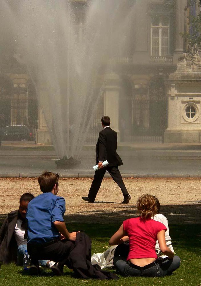 Suit, Parc de Bruxelles - The largest park in central Brussels was once the site of medieval hunting grounds. Here a man in a suit, carrying a roll of papers, strides through the park, past the fountain that stands before the Belgian Parliament. Could he be a legislator, carrying a bill? He seems to have acquired a small audience, dressed for the park instead of for work.