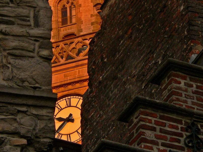 A crack in time - The clock on the towering Belfort peeks between the stones of Ghent's 12th century guildhouses. The Belfort is one of Ghent's most visible landmarks, and was once a center of medieval trade.
