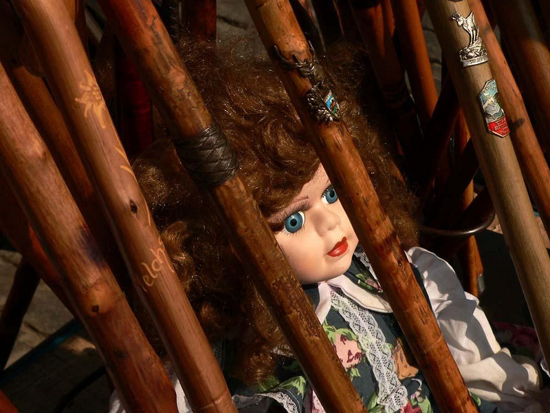 Doll, Place du Jeu de Balle - This doll stares from a prison created by the souvenir walking sticks surrounding it. Only its sale will guarantee freedom.