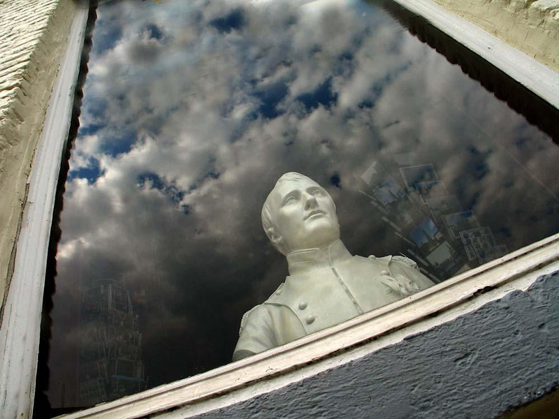 Ghost in the window, Waterloo - Standing between racks of postcards and nested within a layer of reflected clouds, Napoleon haunts a window of a souvenir shop near the battlefield of Waterloo.