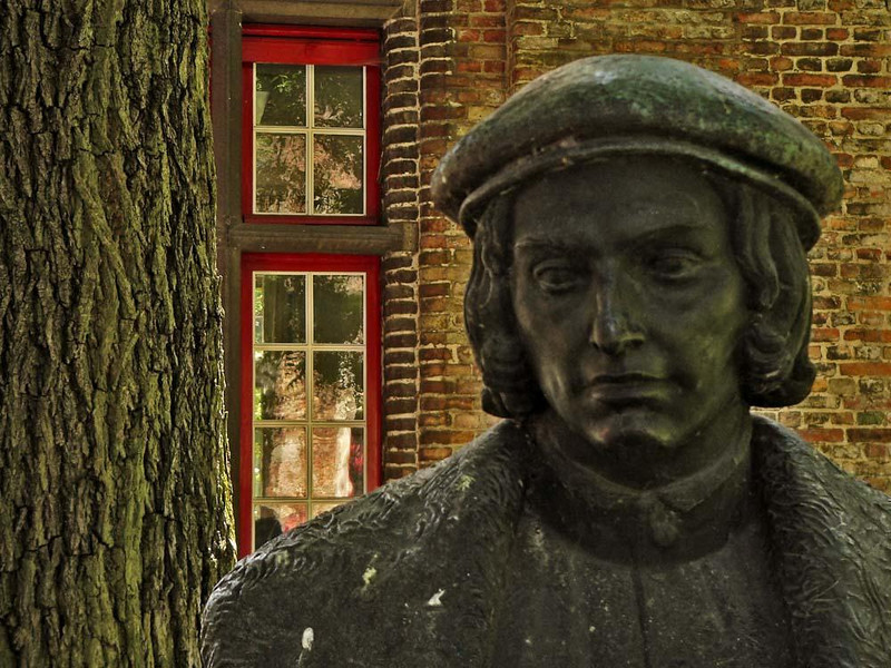 Bruges, sculpture and reflections - I made this photograph not far from the Church of Our Lady -- I was attracted by the placid expression of the sculpture and the vivid reflection of the old tree in the red framed windows.