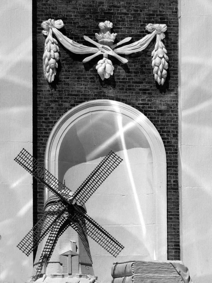 Niche, Leiden - Reflections from a Leiden canal repeat the pattern of the sculptured windmill in this building niche.