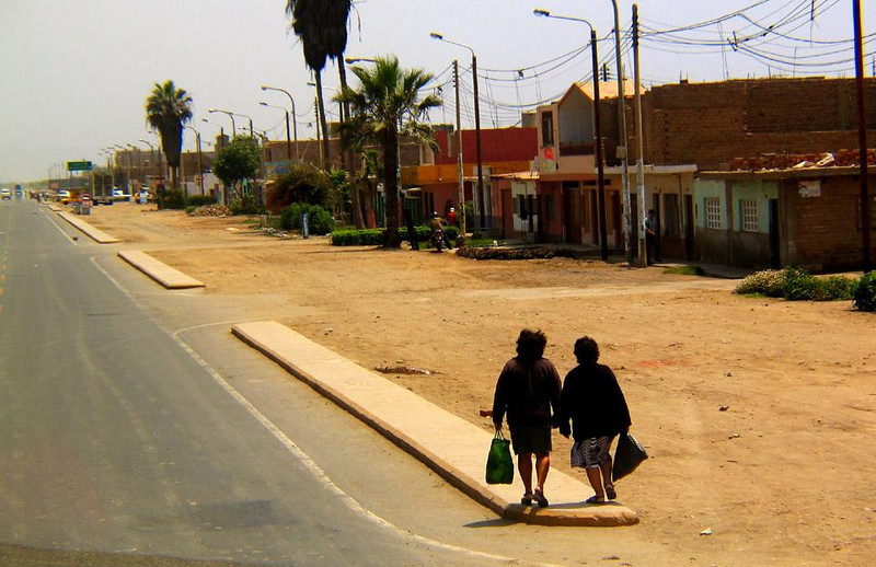 The Shoppers Return, Trujillo, Peru - A pair of shoppers walk home together along the Pan American Highway, which runs through Trujillo. This highway is the main long distance traffic artery of South America. It begins in Alaska and runs all the way to the end of Argentina.